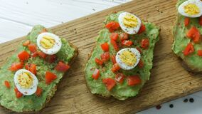 Healthy vegan food. Spread mashed avocado on toasted brown bread with black and red pepper. Making tasty avocado toast