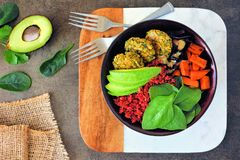 Healthy vegan lunch bowl with falafels, beet quinoa, avocado, and vegetables, above view table scene royalty free stock photography