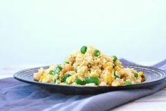Healthy vegan meal with whole grain couscous, chickpeas, sweet corn, peas, green beans on dark plate on grey cloth on wooden backg Stock Images