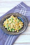 Healthy vegan meal with whole grain couscous, chickpeas, sweet corn, peas, green beans on dark plate on grey cloth on wooden backg Royalty Free Stock Images