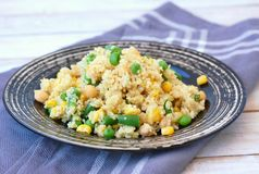 Healthy vegan meal with whole grain couscous, chickpeas, sweet corn, peas, green beans on dark plate on grey cloth on wooden backg Royalty Free Stock Photo