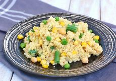 Healthy vegan meal with whole grain couscous, chickpeas, sweet corn, peas, green beans on dark plate on grey cloth on wooden backg Royalty Free Stock Image