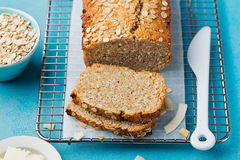 Healthy vegan oat, coconut loaf bread, cake on a cooling rack Grey and blue stone background. Stock Photo