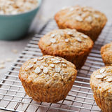 Healthy vegan oat muffins, apple and banana cakes on a cooling rack Grey textile background Royalty Free Stock Photography