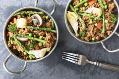 Healthy Vegan Paella. Two bowls of vegan paella with asparagus, mushrooms and artichoke hearts - flat lay royalty free stock photos