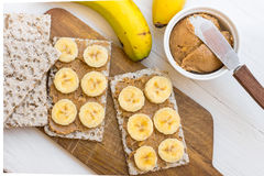 Healthy vegan snack with scandinavian rye crispbread, homemade peanut butter and slices of Canary bananas Royalty Free Stock Image