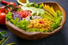 Healthy vegan superfood bowl with quinoa, wild rice, chickpea, tomatoes, avocado, greens, cabbage, lettuce on black stone. Background vegetarian detox stock photos