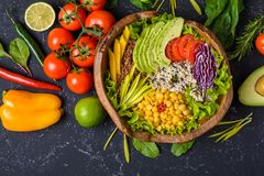Healthy vegan superfood bowl with quinoa, wild rice, chickpea, tomatoes, avocado, greens, cabbage, lettuce on black stone stock photos