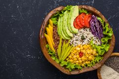 Healthy vegan superfood bowl with quinoa, wild rice, chickpea, tomatoes, avocado, greens, cabbage, lettuce on black stone royalty free stock images