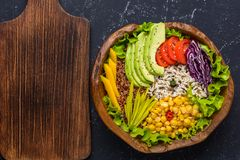 Healthy vegan superfood bowl with quinoa, wild rice, chickpea, tomatoes, avocado, greens, cabbage, lettuce on black stone royalty free stock photos