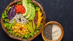 Healthy vegan superfood bowl with quinoa, wild rice, chickpea, tomatoes, avocado, greens, cabbage, lettuce on black stone stock photo