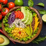 Healthy vegan superfood bowl with quinoa, wild rice, chickpea, tomatoes, avocado, greens, cabbage, lettuce on black stone. Background top view vegetarian detox stock images