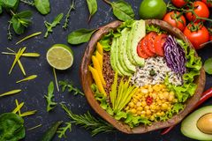 Healthy vegan superfood bowl with quinoa, wild rice, chickpea, tomatoes, avocado, greens, cabbage, lettuce on black stone stock image