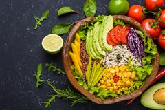 Healthy vegan superfood bowl with quinoa, wild rice, chickpea, tomatoes, avocado, greens, cabbage, lettuce on black stone. Background top view vegetarian detox royalty free stock photography