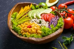 Healthy vegan superfood bowl with quinoa, wild rice, chickpea, tomatoes, avocado, greens, cabbage, lettuce on black stone royalty free stock image