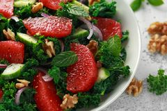 Healthy vegan, vegetarian Grapefruit kale salad with walnuts, red onion and cucumber.  stock photos