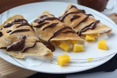 Healthy vegan wheat crepes decorated with chocolate. Wheat crepes with fresh mango and yogurt. royalty free stock image