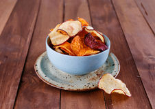 Healthy vegetable chips in a blue cup closeup. Healthy vegetable beetroot, sweet potato and white sweet potato chips in a blue cup closeup on a rustic wooden stock photography