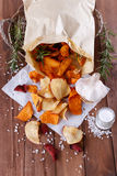 Healthy vegetable chips on paper with sea salt, rosemary and garlic. Healthy vegetable beetroot, sweet potato and white sweet potato chips on paper with sea salt royalty free stock photography
