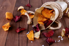 Healthy vegetable chips in a paper wrap with sea salt. Healthy vegetable beetroot, sweet potato and white sweet potato chips with sea salt in a vintage paper stock photo
