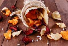 Healthy vegetable chips in a paper wrap with sea salt. Healthy vegetable beetroot, sweet potato and white sweet potato chips with sea salt in a vintage paper stock photography