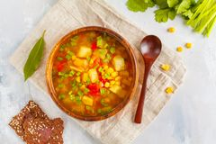 Healthy vegetable corn soup in a wooden bowl with flax crispy br. Healthy bright vegetable corn soup with a root of a herring, pepper, an onion in a wooden bowl royalty free stock image