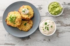 Healthy vegetable rosti from cauliflower and parmesan cheese wit. H dips from sour cream and avocado, parsley garnish, blue plate on a bright rustic wooden table Royalty Free Stock Images