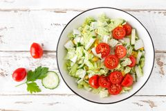 Healthy vegetable salad of chinese cabbage, corn, cucumbers and tomatoes. Delicious vegetarian dietary lunch. Vegan food. Top view. Flat lay stock image