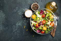 Healthy vegetable salad of fresh tomato, cucumber, onion, spinach, lettuce and pumpkin seeds in bowl. Diet menu. Top view with cop. Y space stock photos