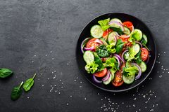 Healthy vegetable salad of fresh tomato, cucumber, onion, spinach, lettuce and sesame on plate. Diet menu. Top view stock image
