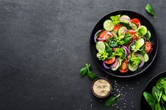 Healthy vegetable salad of fresh tomato, cucumber, onion, spinach, lettuce and sesame on plate. Diet menu. Top view royalty free stock photo