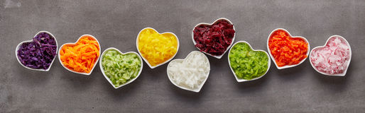 Healthy vegetables banner concept. Healthy grated vegetables of different colors in heart-shaped bowls in funny long row as wide banner concept Royalty Free Stock Image