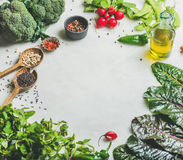 Healthy vegetables, greens and grains, copy space. Fresh raw greens, vegetables, olive oil and grains over light grey marble kitchen countertop, copy space Royalty Free Stock Photo