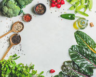 Healthy vegetables, greens and grains, copy space, top view. Fresh raw greens, vegetables, olive oil and grains over light grey marble kitchen countertop, top Stock Photo