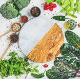 Healthy vegetables, greens and grains, round board in center. Fresh raw greens, vegetables, olive oil and grains over light grey marble kitchen countertop, round Stock Photography