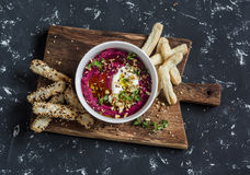 Healthy vegetarian beet hummus and puff pastry bread sticks on a wooden rustic board. On a dark background Stock Photos