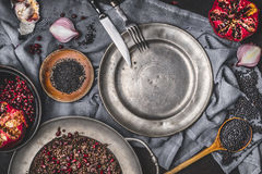 Healthy vegetarian black lentil salad with pomegranate on kitchen table with empty plate and cutlery , top view. Stock Image