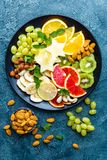 Healthy vegetarian bowl dish with fresh fruits and nuts. Plate with raw apple, orange, grapefruit, banana, kiwi, lemon, grape, alm royalty free stock photography