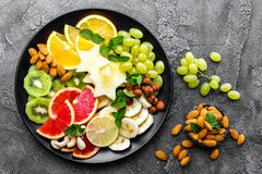 Healthy vegetarian bowl dish with fresh fruits and nuts. Plate with raw apple, orange, grapefruit, banana, kiwi, lemon, grape, alm. Ond, hazelnut and cashew nuts stock photos