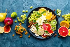 Healthy vegetarian bowl dish with fresh fruits and nuts. Plate with raw apple, orange, grapefruit, banana, kiwi, lemon, grape, alm royalty free stock photo