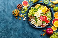 Healthy vegetarian bowl dish with fresh fruits and nuts. Plate with raw apple, orange, grapefruit, banana, kiwi, lemon, grape, alm stock photos