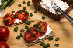Healthy and vegetarian breakfast with crispbread, quark, tomatoes and spring onions stock photos