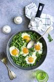 Healthy vegetarian breakfast : fried eggs and asparagus bean in. A skillet over light grey slate, stone or concrete backgrond.Top view stock images