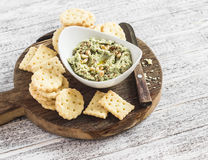Healthy vegetarian broccoli and pine nuts hummus and homemade cheese biscuits on a wooden rustic board. Royalty Free Stock Photography