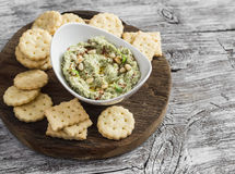 Healthy vegetarian broccoli and pine nuts hummus and homemade cheese biscuits on a wooden rustic board. Royalty Free Stock Images