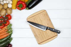 Healthy vegetarian cooking cutting board with knife and vegetabl Royalty Free Stock Images
