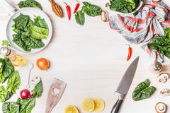 Healthy vegetarian cooking with spinach leaves on white wooden background with kitchen knife and ingredients, top view frame. Royalty Free Stock Images