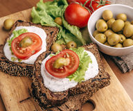 Healthy and Vegetarian diet breakfast concept. Homemade bread with cheese cream. Lettuce, tomatoes and green olives in bowl. Top view Royalty Free Stock Image