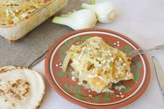 Healthy vegetarian dinner: oven baked fennel bulbs with potatoes. Royalty Free Stock Photos