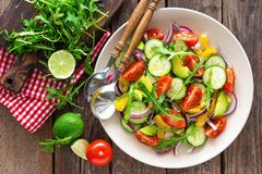 Healthy vegetarian dish, vegetable salad with fresh tomato, cucumber, bell pepper, red onion, avocado and arugula stock photo